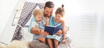 Padre de la familia que lee al libro de niños en tienda en casa Imagenes de archivo