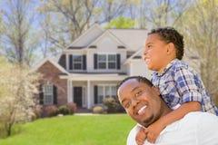 Padre de la raza mixta e hijo activos delante de la casa Imagen de archivo libre de regalías