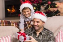 Padre de ofrecimiento del hijo un regalo de la Navidad en el sofá Fotografía de archivo libre de regalías