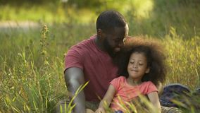 Padre del genitore non coniugato che prende cura di piccola figlia fatta tesoro con capelli ricci video d archivio
