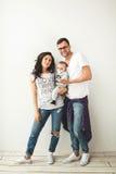 Padre del inconformista, madre que celebra al bebé lindo sobre el backgrou blanco fotografía de archivo