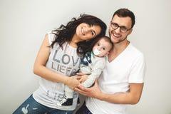 Padre del inconformista, madre que celebra al bebé lindo sobre el backgrou blanco Fotos de archivo libres de regalías