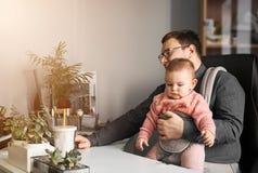 Padre dell'uomo con il bambino in trasportatore che funziona a ufficio o casa con il computer allo scrittorio, genitore in uffici fotografia stock