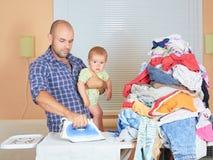 Padre dell'uomo e figlio caucasici in sue mani, vestiti rivestiti di ferro in Fotografia Stock