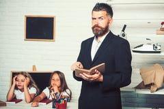Padre della famiglia di lettura per le figlie a scuola immagine stock libera da diritti