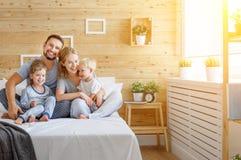 Padre della madre della famiglia e bambini felici derivato e figlio a letto Immagine Stock