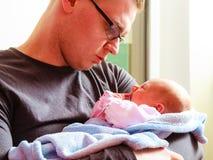 Padre deteniendo delicado a su bebé recién nacido Fotos de archivo