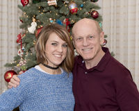 Padre di 69 anni e bella figlia di 43 anni che stanno davanti ad un albero di Natale Fotografia Stock Libera da Diritti