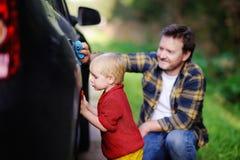Padre di medio evo con la sua automobile di lavaggio del figlio del bambino insieme all'aperto Fotografia Stock