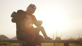 Padre di Slomo allegro che abbraccia piccolo figlio che si siede sul banco sul campo alla fine di tempo di alba su Concetto di archivi video