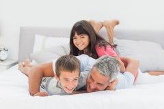 Padre divertendosi con i suoi bambini sul letto fotografie stock