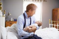 Padre Dressed For Work que detiene al bebé en dormitorio Imagen de archivo libre de regalías