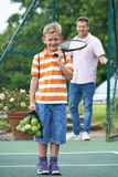 Padre Dropping Son Off para la lección de tenis Imagen de archivo