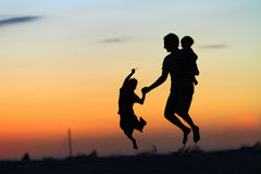 Padre e bambini che saltano al tramonto Fotografia Stock Libera da Diritti