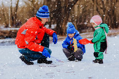 Padre e bambini che scavano neve in natura di inverno Fotografie Stock