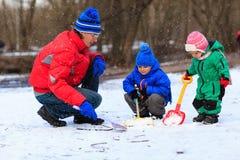 Padre e bambini che scavano neve nel parco di inverno Immagini Stock Libere da Diritti