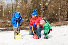 Padre e bambini che scavano neve nel parco di inverno Fotografia Stock Libera da Diritti