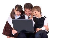 Padre e bambini sul computer portatile Fotografia Stock Libera da Diritti