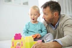 Padre e bambino che giocano insieme ai blocchetti del giocattolo Immagini Stock