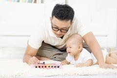 Padre e bambino che giocano lo strumento di musica Fotografia Stock