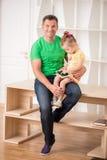 Padre e bambino che per mezzo della compressa elettronica a casa Immagini Stock