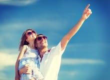 Padre e bambino felici in occhiali da sole sopra cielo blu Immagini Stock Libere da Diritti