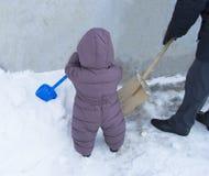 Padre e bambino insieme per pulire le pale della neve Fotografia Stock Libera da Diritti