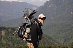 Padre e bambino nello zaino che fa un'escursione montagna Immagine Stock