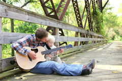 Padre e bambino piccolo che giocano chitarra fuori al parco Fotografia Stock