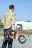 Padre e bici dei bambini Fotografie Stock