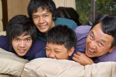 Padre e figli che hanno divertimento in camera da letto Fotografia Stock Libera da Diritti