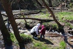 Padre e figlia che camminano vicino al fiume della foresta fotografia stock libera da diritti