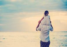 Padre e figlia che giocano insieme alla spiaggia al tramonto fotografie stock libere da diritti