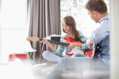 Padre e figlia che giocano le chitarre elettriche a casa Fotografia Stock