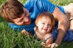 Padre e figlia che giocano nell'erba Fotografia Stock Libera da Diritti
