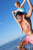 Padre e figlia che hanno divertimento sulla spiaggia Immagini Stock