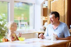 Padre e figlia che mangiano prima colazione Fotografie Stock Libere da Diritti