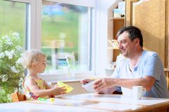 Padre e figlia che mangiano prima colazione Fotografia Stock