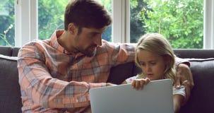 Padre e figlia che per mezzo del computer portatile sul sofà a casa 4k video d archivio