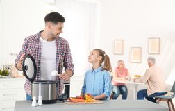 Padre e figlia che preparano alimento con il multi fornello in cucina immagine stock libera da diritti