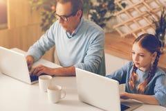Padre e figlia che rifiutano di chiacchierare mentre per mezzo dei computer portatili Fotografie Stock Libere da Diritti