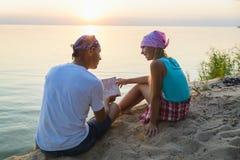Padre e figlia che riposano e che esaminano mappa Concetto di turismo e di corsa Fotografia Stock