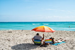 Padre e figlia che si rilassano sotto l'ombrello arancio sulla spiaggia sabbiosa Immagine Stock Libera da Diritti