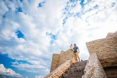 Padre e figlia che stanno sulla struttura di pietra su un backgro Fotografie Stock Libere da Diritti