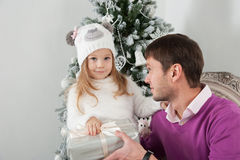 Padre e figlia con il regalo vicino all'albero di Natale Fotografia Stock