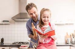 Padre e figlia divertendosi nella cucina - cottura immagini stock libere da diritti