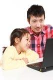 Padre e figlia giapponesi sul computer portatile Fotografia Stock