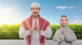 Padre e figlia musulmani asiatici sorridenti che pregano insieme fotografia stock