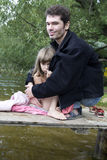 Padre e figlia sul ponticello al fiume Fotografie Stock