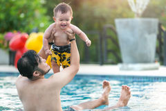 Padre e figlio allegri divertendosi in acqua Fotografia Stock